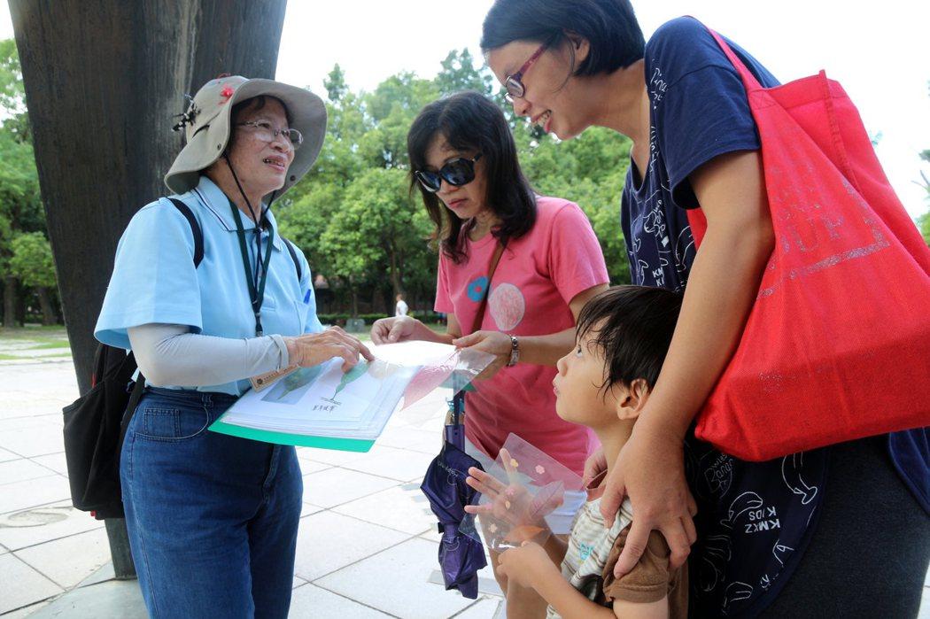 70歲佘善(左)自繪教材,導覽說明高雄都會公園從掩埋場變身生態公園。記者徐如宜/攝影