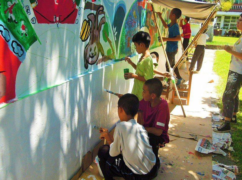 崑山科技大學視覺傳達設計系學生,今年暑假教台東泰源國小學生繪畫,讓校園圍牆煥然一新,變得色彩繽紛。圖/教育部提供