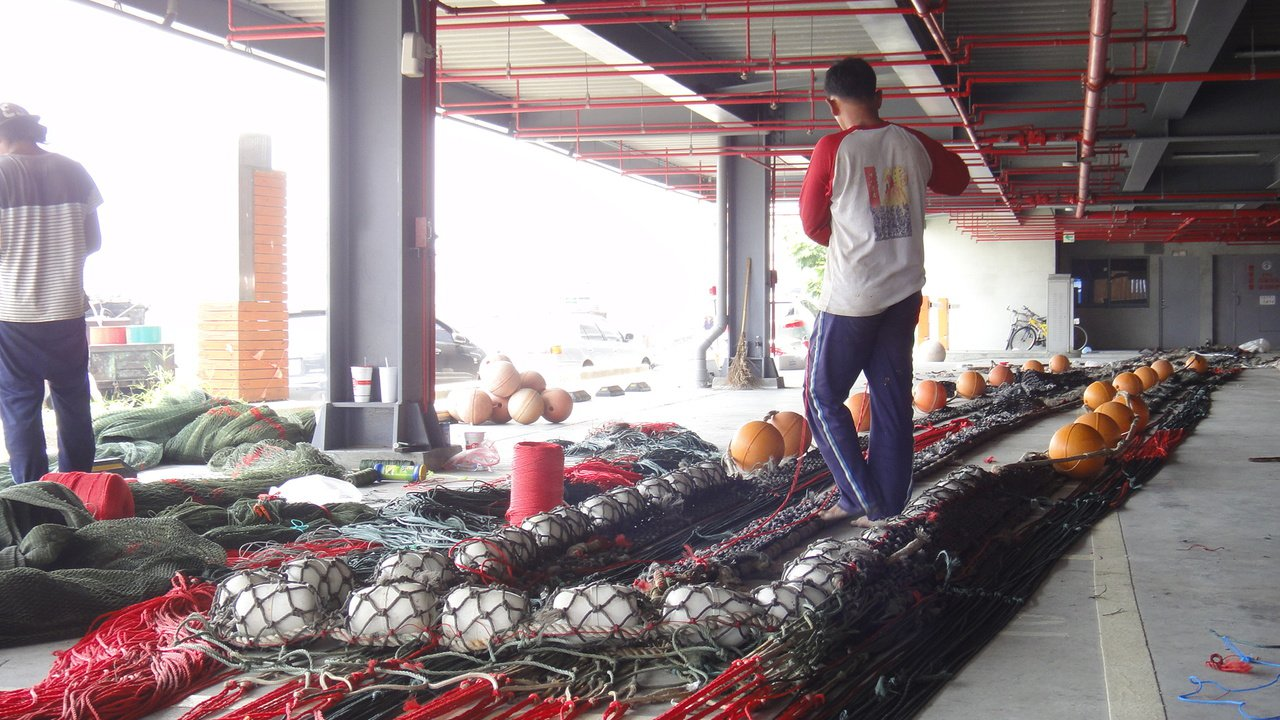 東港漁港立體停車場長達一年時間閒置不用,反成外籍漁工修補魚網的場所。記者蔣繼平/...