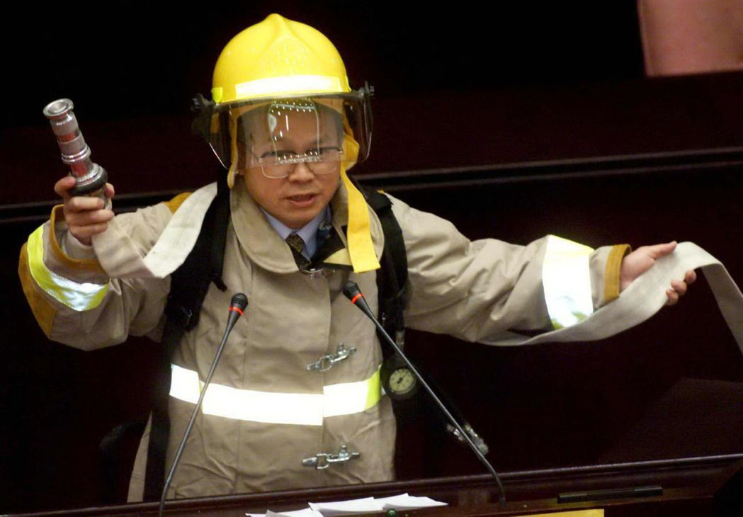 立委林政則背著30多公斤消防隊員的設備,呼籲大家應向辛苦的打火英雄致敬。 報系資...