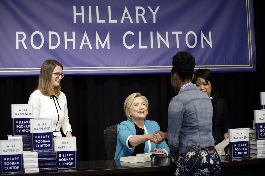 柯林頓在簽書會上跟現場久候的支持者握手致意。 美聯社