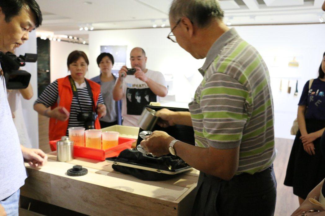 資深相館人涂寬裕(右),在展場親自動手示範沖洗照片。記者林麒瑋/攝影