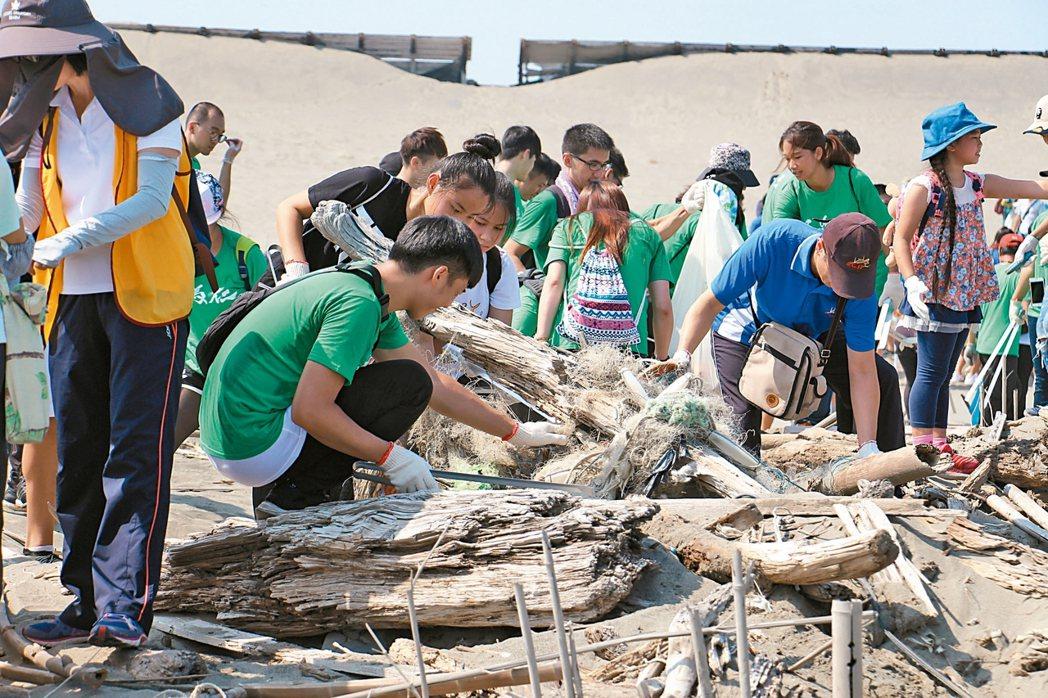 海巡署、台北市福智佛教基金會與聯合報願景工程工作室昨天在清水區高美濕地淨灘,共有...