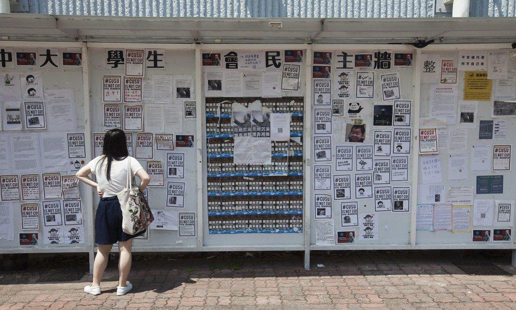 中大學生會副會長李振勇表示,學生會將24小時看守民主牆。圖為一名學生正在觀看中大...