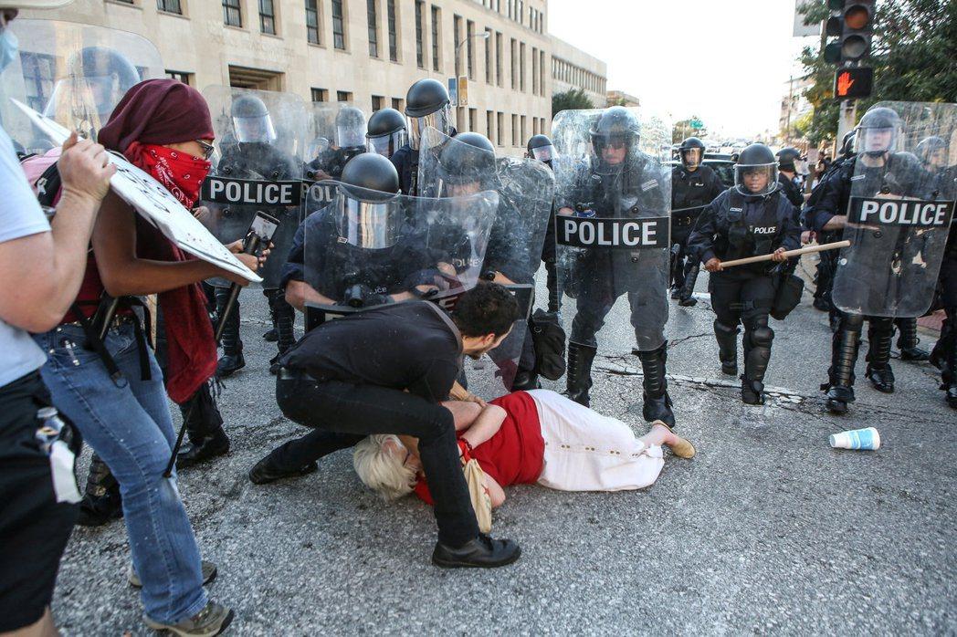 一名抗議的婦女被警察推倒,其餘抗議者上前搶救。路透