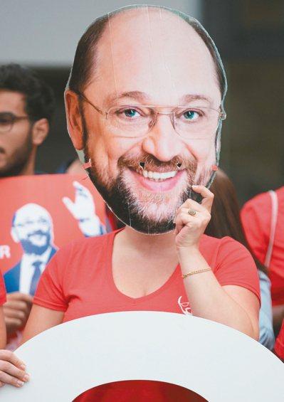 日前德國社會民主黨總理候選人舒茲與梅克爾進行電視辯論前,舒茲支持者戴著他的面具。...