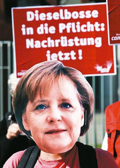 民眾戴著德國總理梅克爾的面具,抗議柴油車排放對德國空氣造成汙染。 歐新社