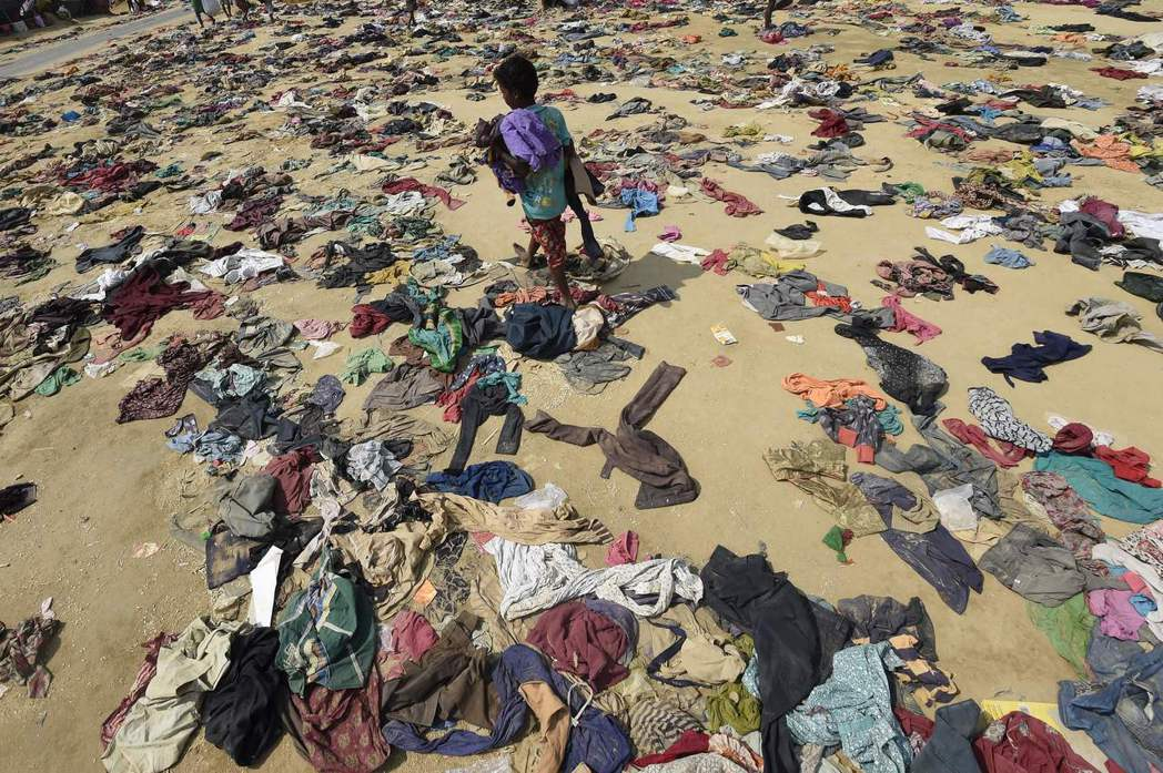 一名洛興雅男孩16日走過孟加拉難民營中難民丟棄滿地的衣服。(法新社)