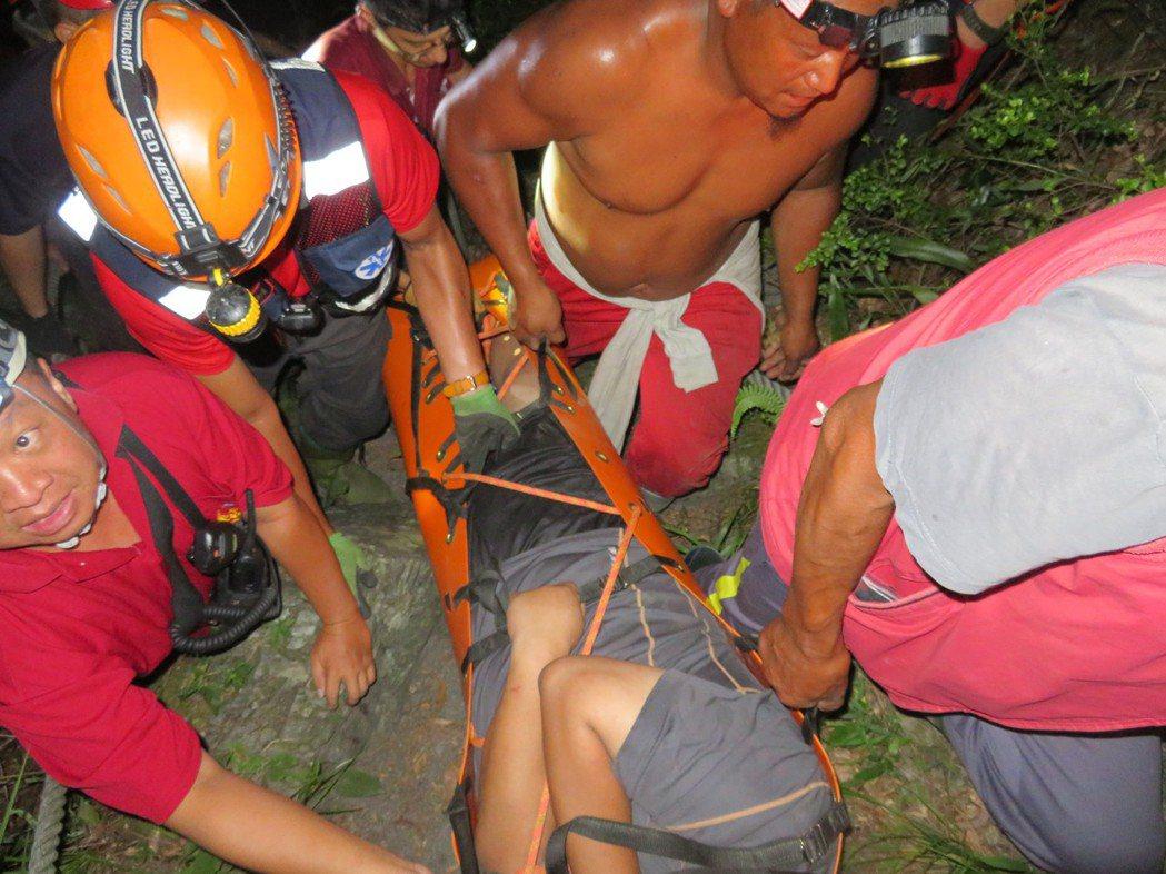 台東南橫栗松溫泉昨天1名許男受困,救難人員將他連拉帶拖,協助他脫困。圖/關山消防...
