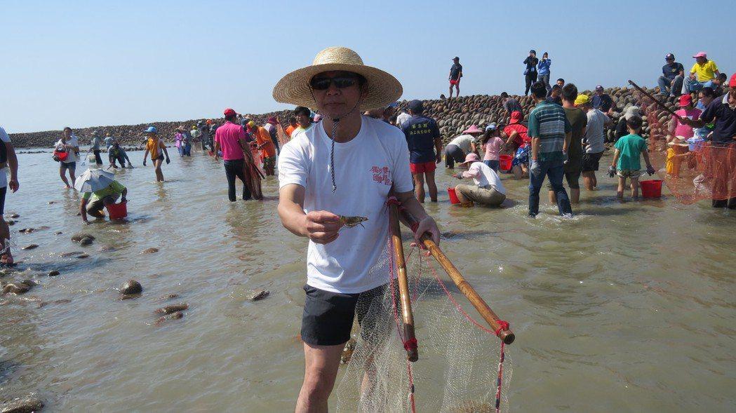 苗栗縣後龍鎮長朱秋隆小試身手,展示捕到的海水草蝦。記者范榮達/攝影