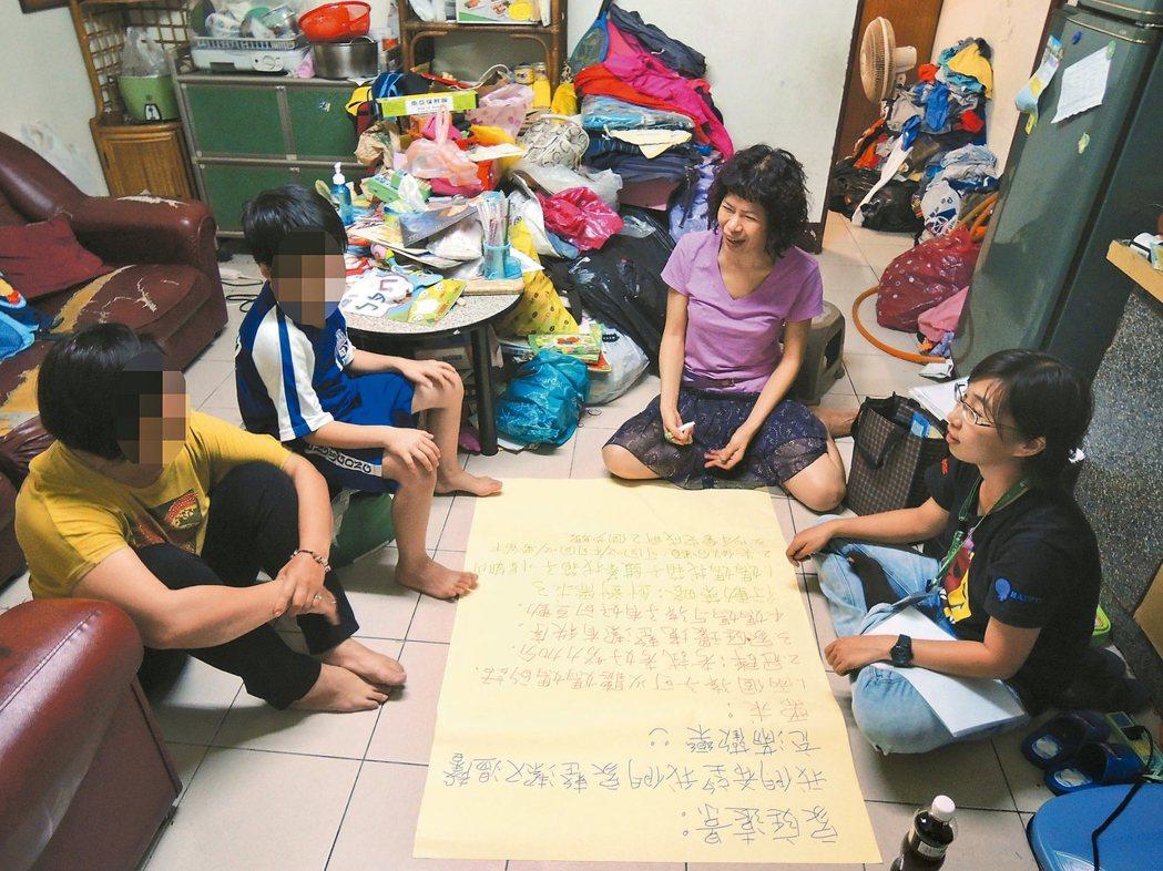 家扶社工協助處理家庭問題時,會與個案家庭成員召開「家庭會議」,並以大字報列出欲改...