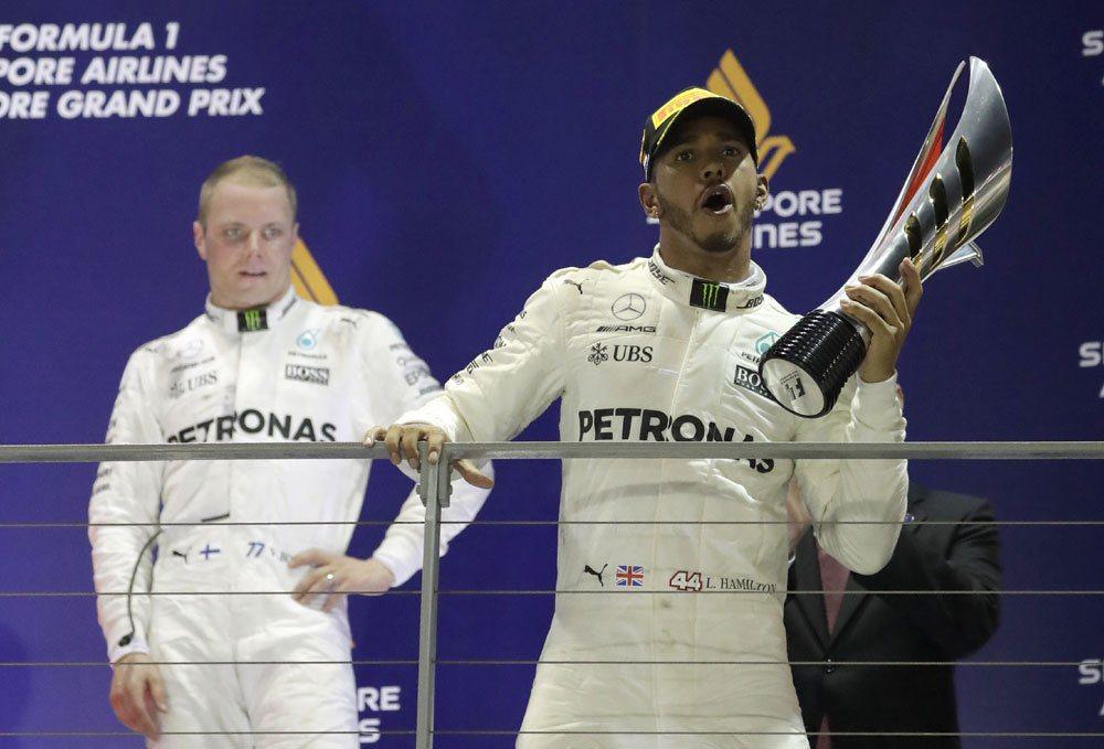 賓士車隊英國車手韓密爾頓(右)在一級方程式賽車新加坡大獎賽奪冠。 美聯社