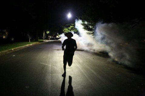 17日深夜,在美國密蘇里州聖路易市的街頭,一名示威抗議者正逃離警察的催淚瓦斯攻擊...