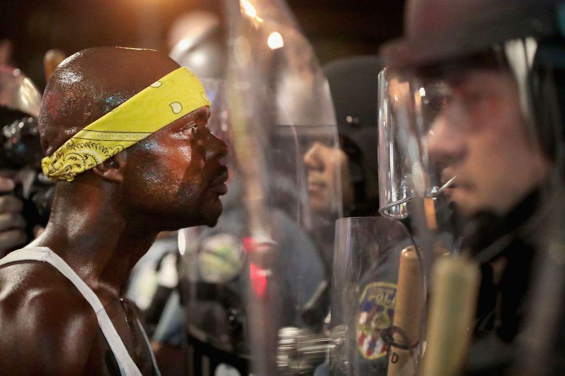 聖路易的警民衝突升高,一名非裔美國人(左)與鎮暴警察在街頭對峙。 圖/法新社