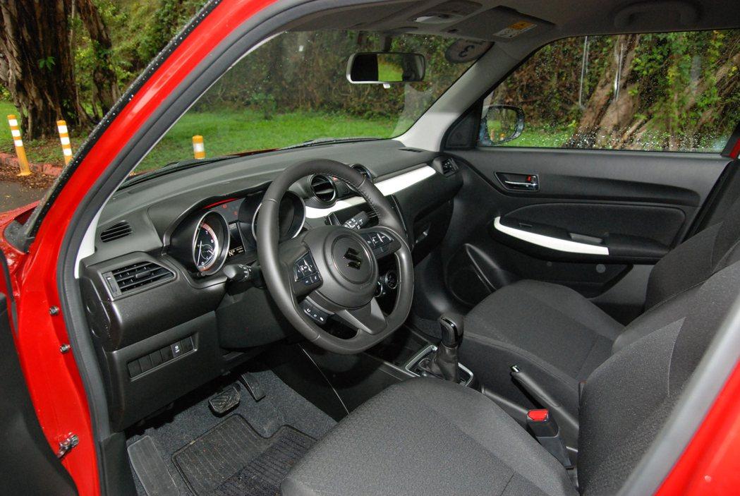 Suzuki Swift 內裝採用硬質塑料、不織布椅,搭配白色車門飾板與鋼琴烤漆...