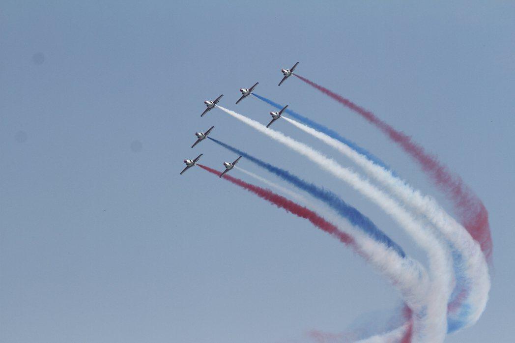 「雷虎特技小組」7機編隊實施特技表演,搭配紅、藍、白3色彩煙,在藍天中畫出美麗弧...
