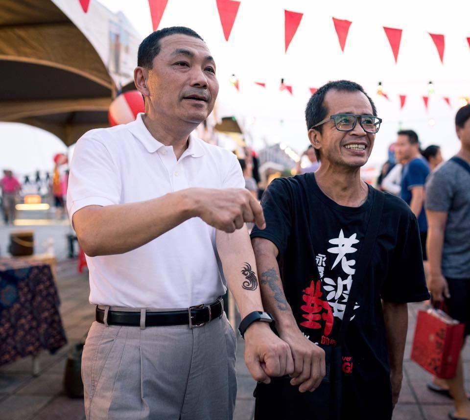 新北市副市長侯友宜在臉書PO了一張與一位男子的合照,對方身上的T-shirt上大...