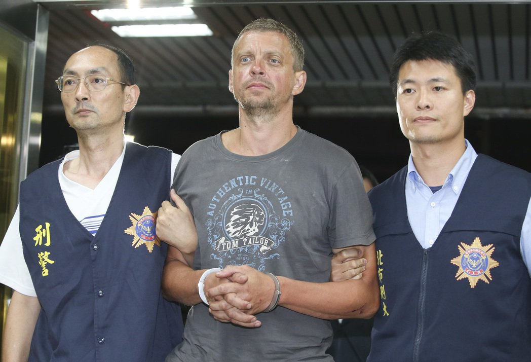 一銀盜領案主嫌安德魯(中)在宜蘭落網,由員警押回台北市刑大。 本報資料照片
