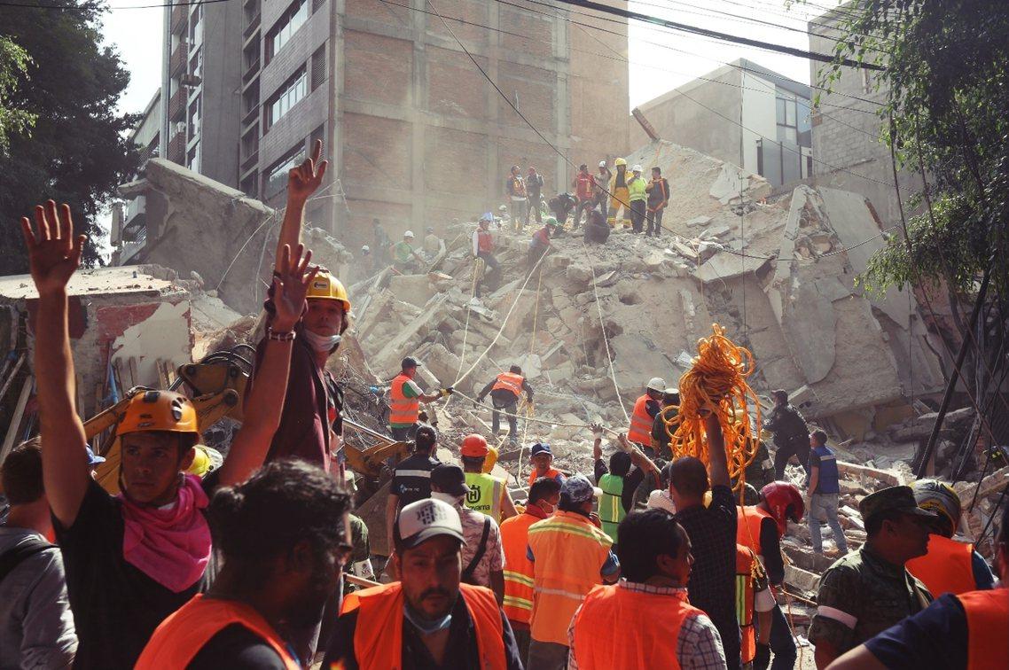 強震之後,墨西哥城全市救難,而為了聽見瓦礫堆下的生還求救者,救難隊都舉起手來向周...