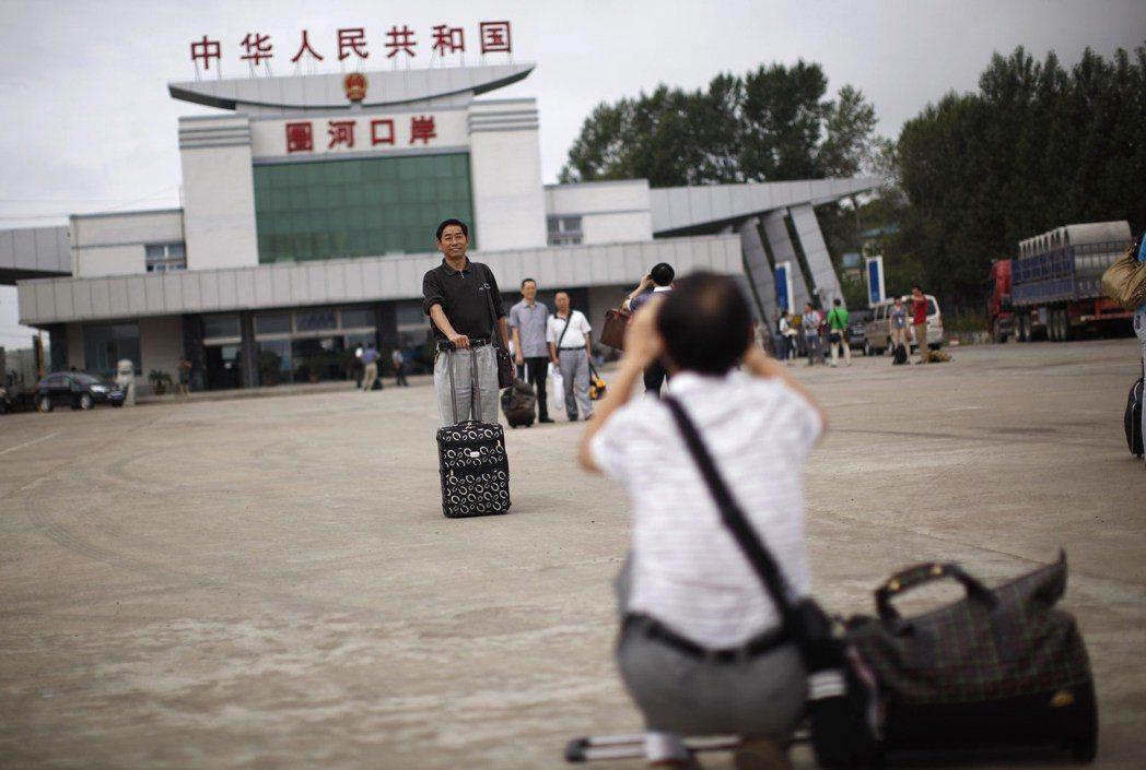 一名中國大陸遊客在中朝邊界的琿春市圈河口岸拍照留念。 (路透)