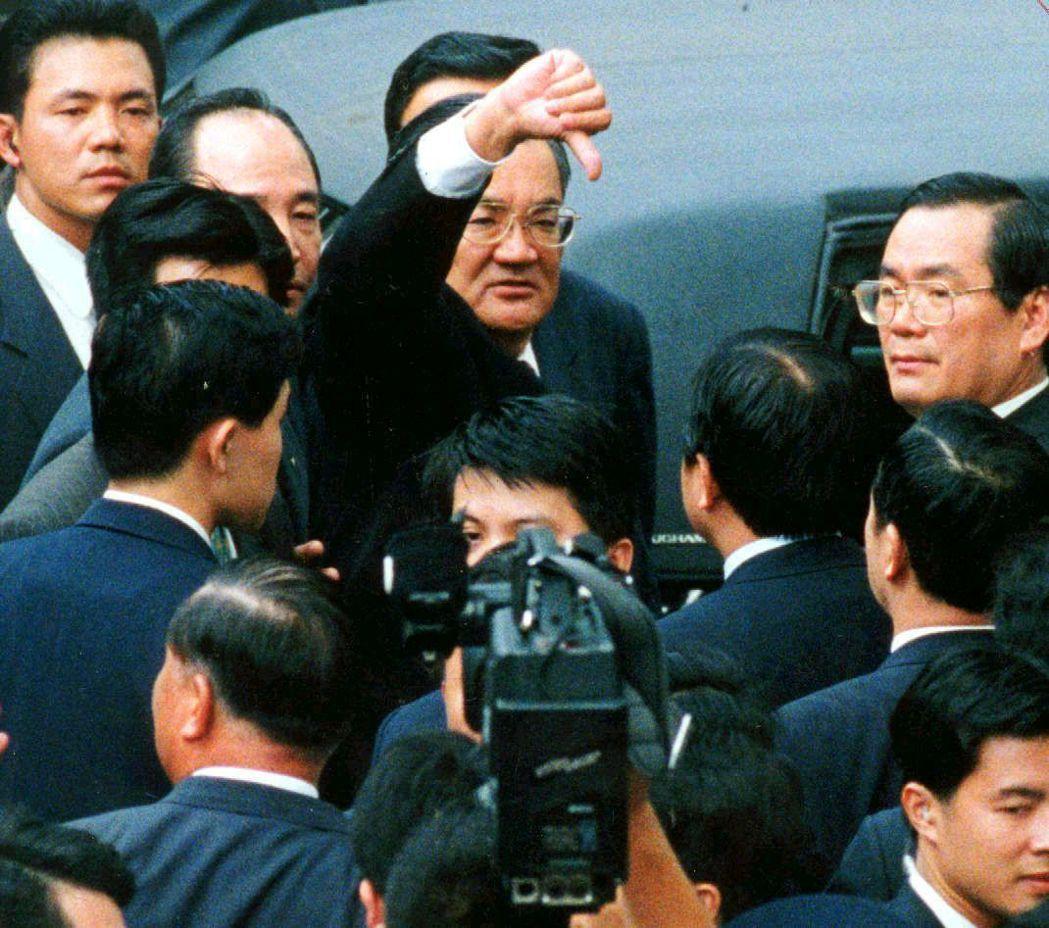 1996年副總統兼行政院長連戰,在立法院側門遭民進黨立委人牆阻擋。連戰倒豎拇指,...