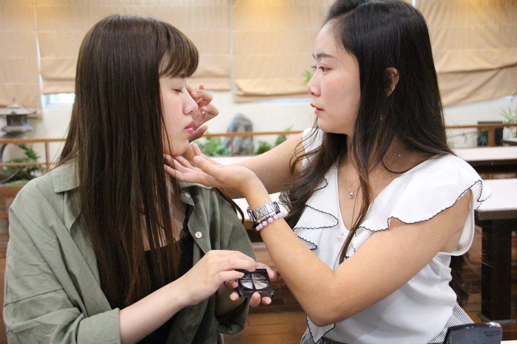 女大生之間常可見互相協助化妝。 記者洪上元/攝影