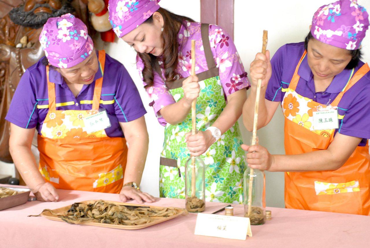 將撕成長條狀酸菜,放置進玻璃瓶內醃製福菜。圖/桃園市客家事務局提供