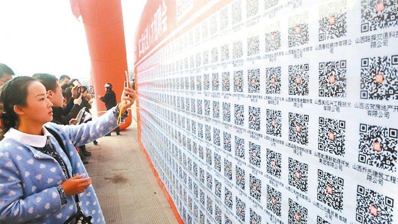 大陸的一面牆上,貼滿人才招募QR碼。 (圖/美國有線電視新聞網)