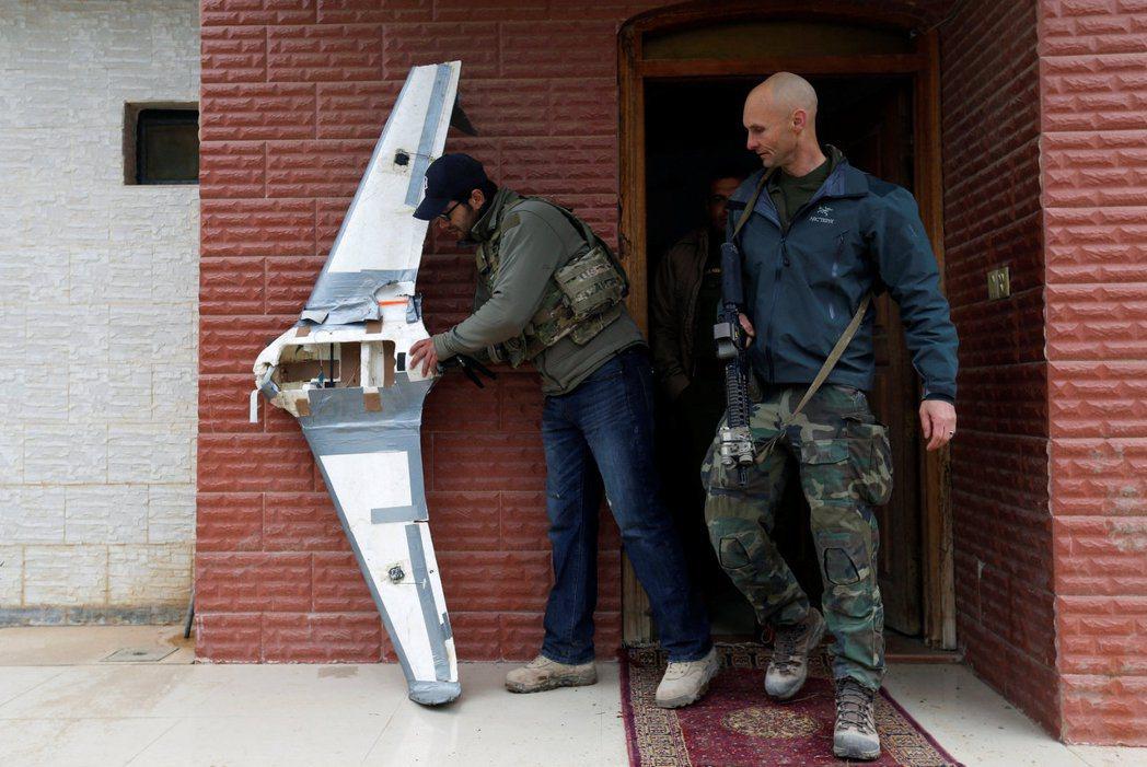 美國特戰部隊人員在伊拉克摩蘇爾檢查一架IS用來投放炸彈的無人機。 路透