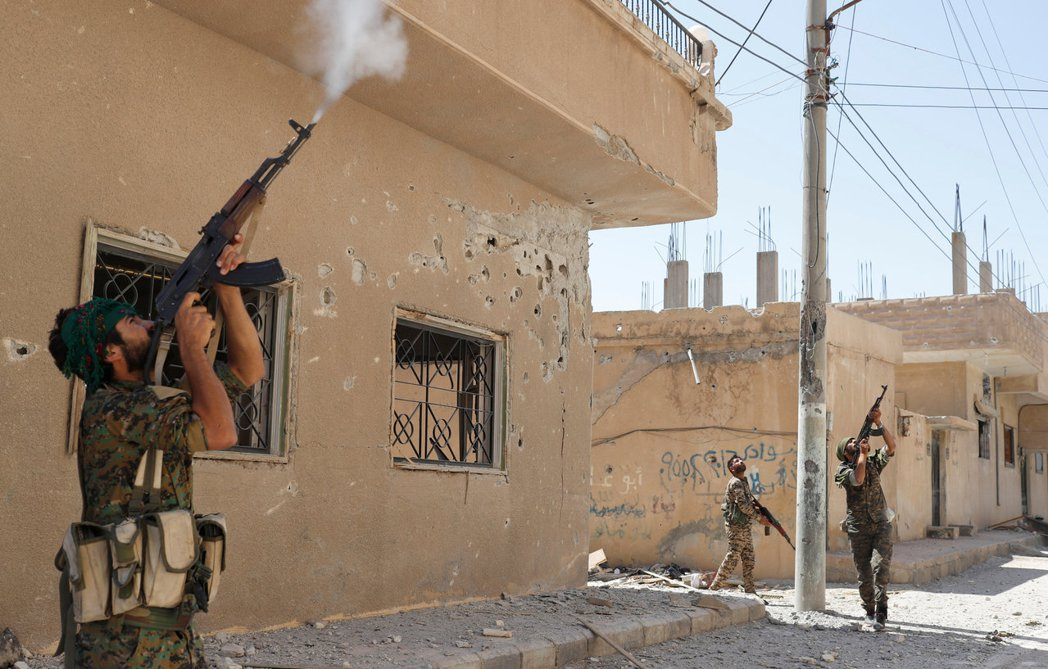 協助美國對抗IS的敘利亞庫德族民兵以步槍射擊IS無人機。 路透
