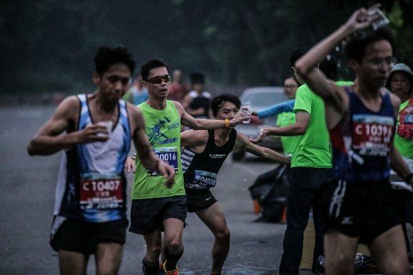 頂著33度以上高溫跑馬拉松,許多選手都熱得用水淋溼身體、頭頂降溫。 (主辦單位提...