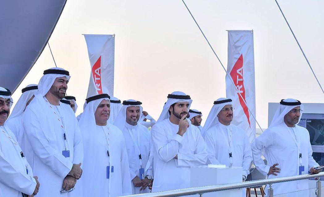 杜拜王儲哈姆丹(中)與隨行人員站在看台上。 法新社