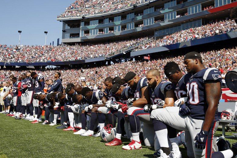 新英格蘭愛國者隊的球員以單膝跪地方式表達抗議。 圖/美聯社