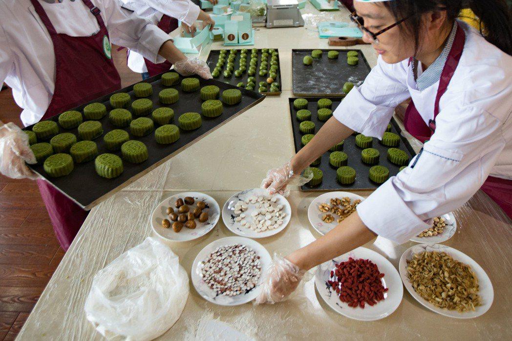 南京中國藥科大學藥學院的大學生現場製作「居家版」中藥餡月餅,在月餅中添加百合、山...