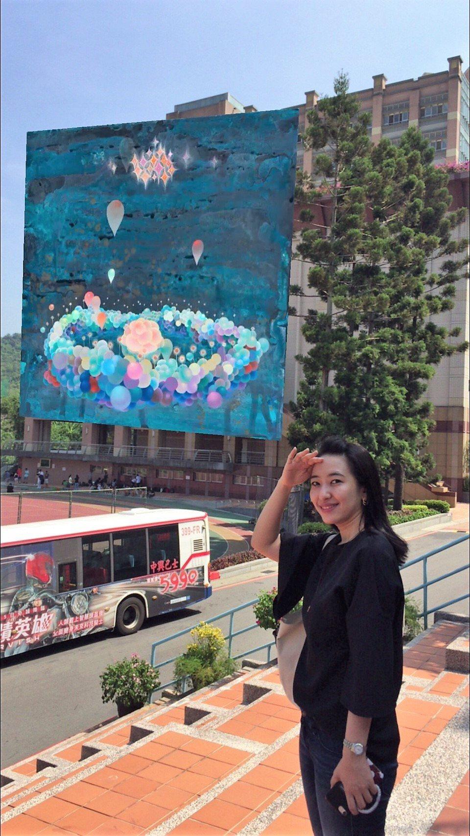 透過手機螢幕,東吳大學校舍牆上出現大幅畫作。圖/東吳大學提供