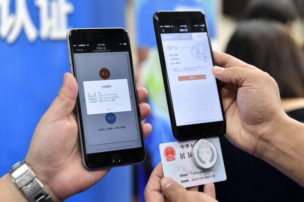 警方26日使用身分證微型識別器將身分證信息錄入「微警認證」APP。(中新社) 中...