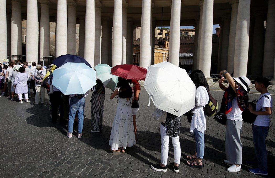 義大利今年八月初的熱浪,讓梵蒂岡聖伯多祿廣場遊客紛紛拿傘遮擋毒辣的太陽。 路透