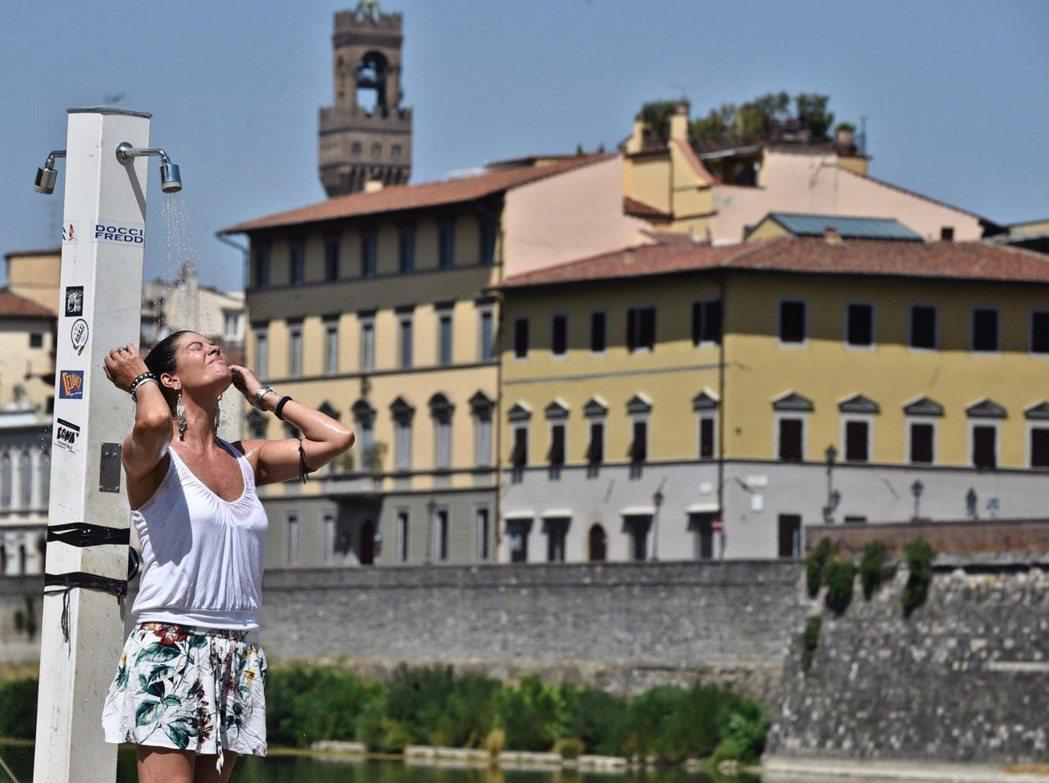 今年八月初義大利遭熱浪侵襲,佛羅倫斯一名女子沖水消暑。 歐新社