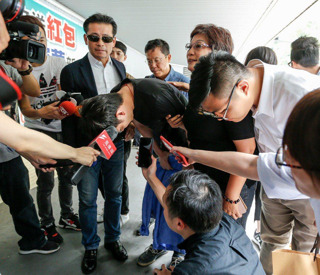李新的兒子李柏毅(中)下午帶著父親的兩套襯衫到第二殯儀館,面對媒體追問,李柏毅9...