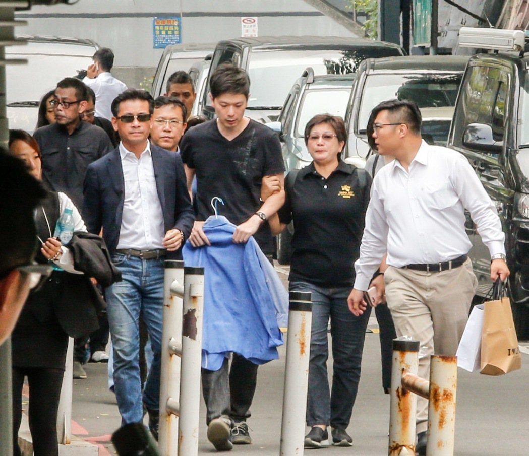 李新的兒子李柏毅(中)下午帶著父親的兩套襯衫到第二殯儀館,面對媒體追問,李柏毅只...