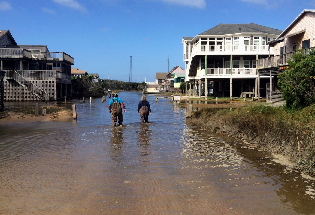 一對情侶27日在美國北卡州巴克斯頓(Buxton)被水淹的道路上行走。美聯社