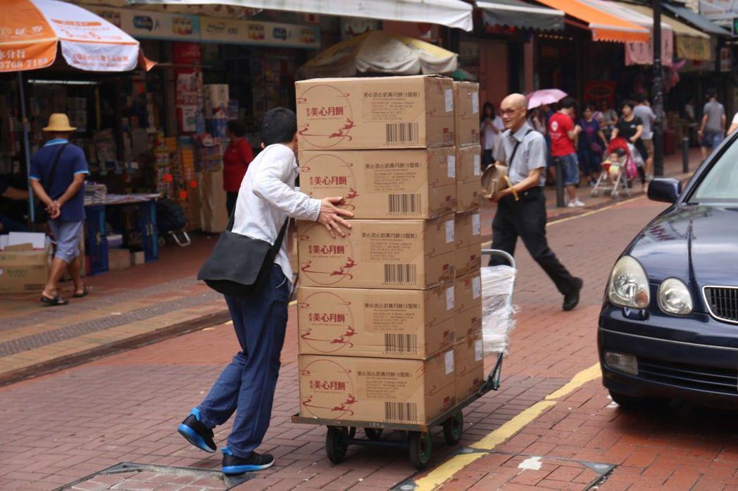 有人手持百張月餅券、帶著手推車從西餅店一口氣運走10箱八個裝的流心奶黃月餅。圖擷...