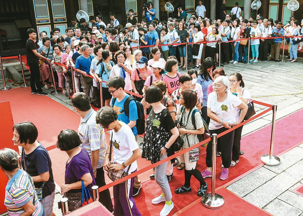 祭孔這天許多民眾一早趕至台北孔廟排隊準備領取智慧毛與智慧糕。 記者鄭清元/攝影