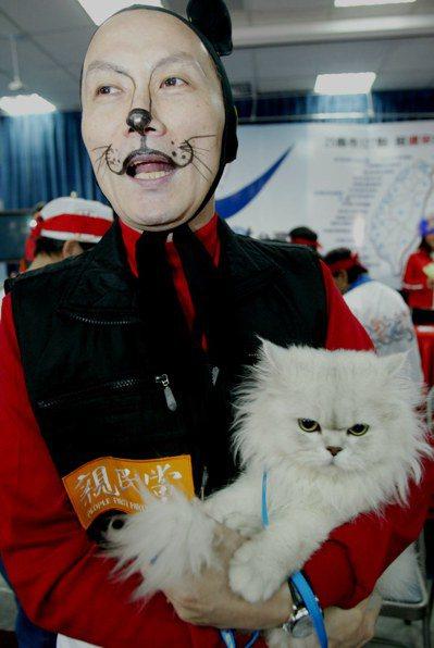 李新2004年擔任台北市議會副議長時,扮成貓咪的造型手抱貓咪為藍營發動的「313...