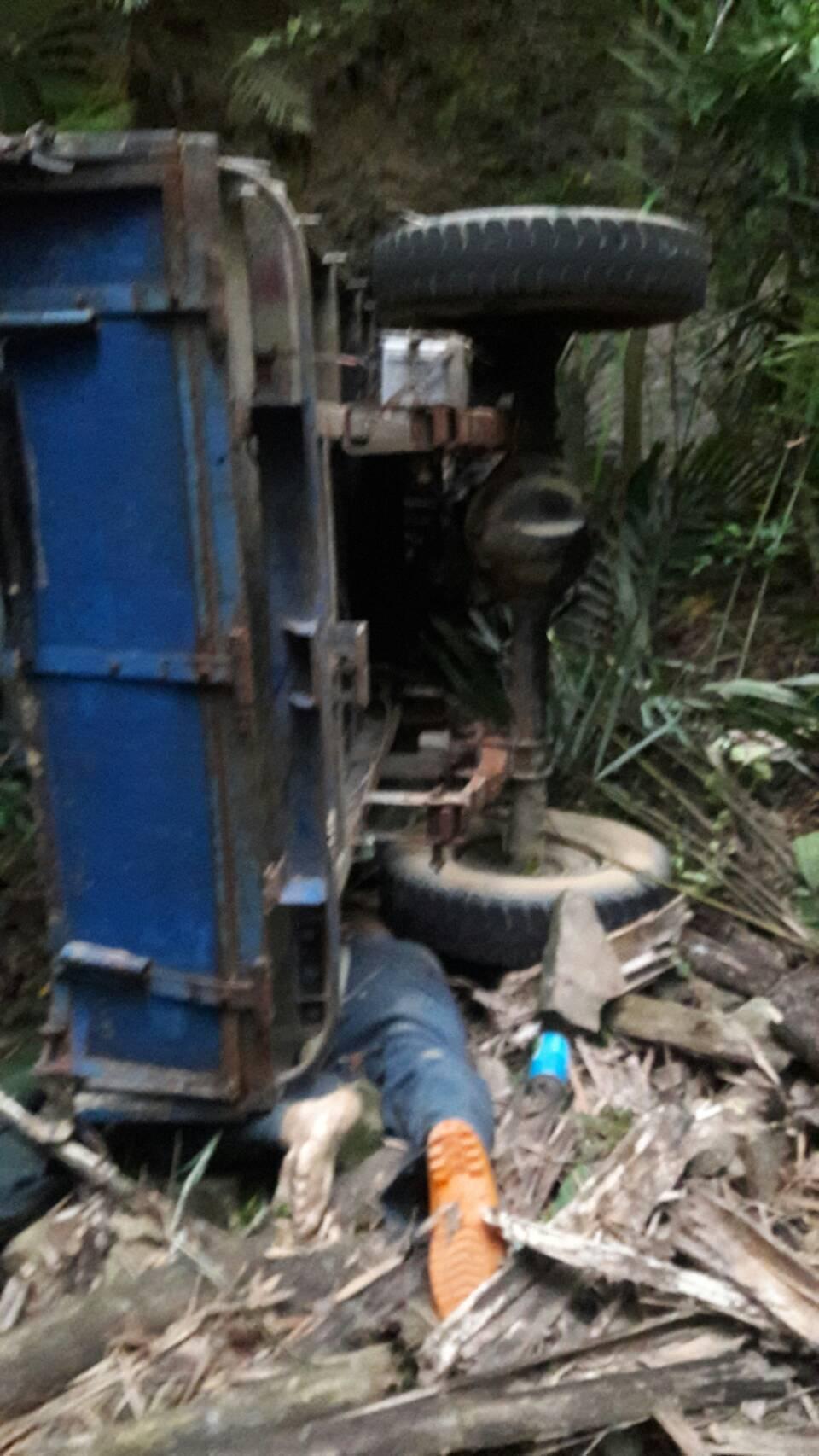 吳姓老人駕拼裝車翻落山谷,被壓在車底。圖/消防局提供