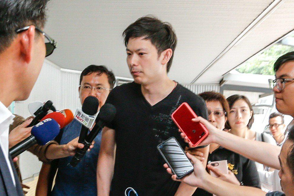 李新的兒子李柏毅(中)昨天下午帶著父親的兩套襯衫到第二殯儀館,面對媒體追問,李柏...