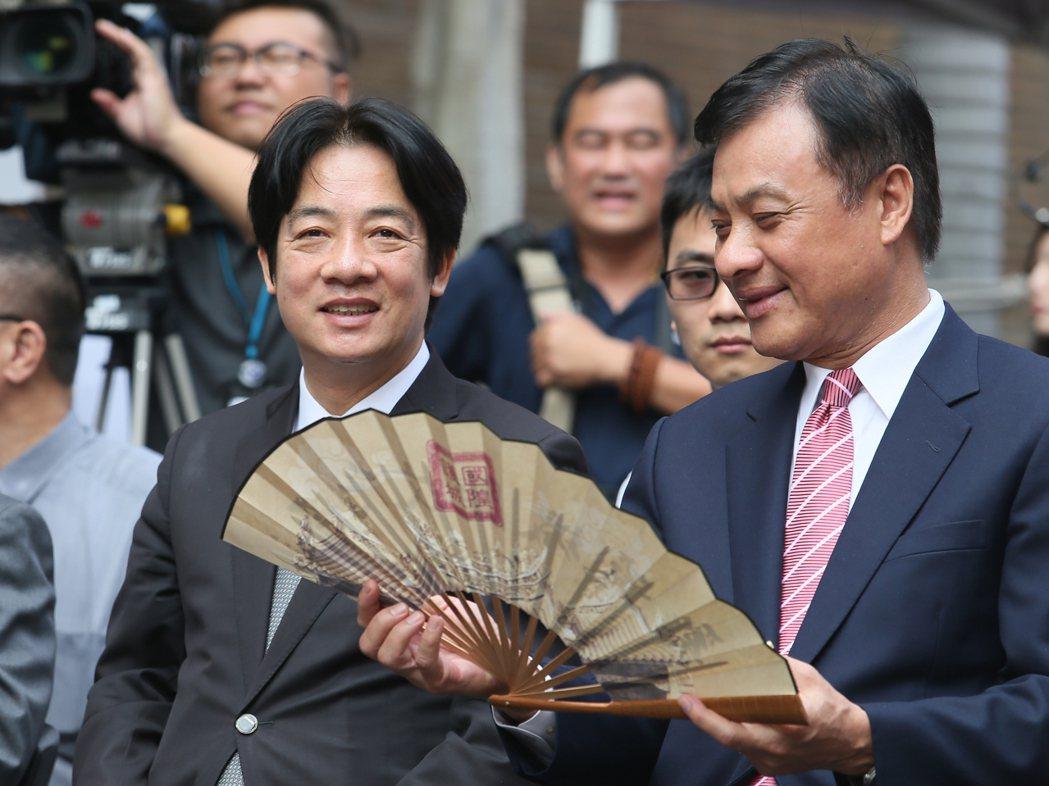 行政院長賴清德(左)與立法院長蘇嘉全(右)一同出席活動,看著印有基隆文化的扇子一...