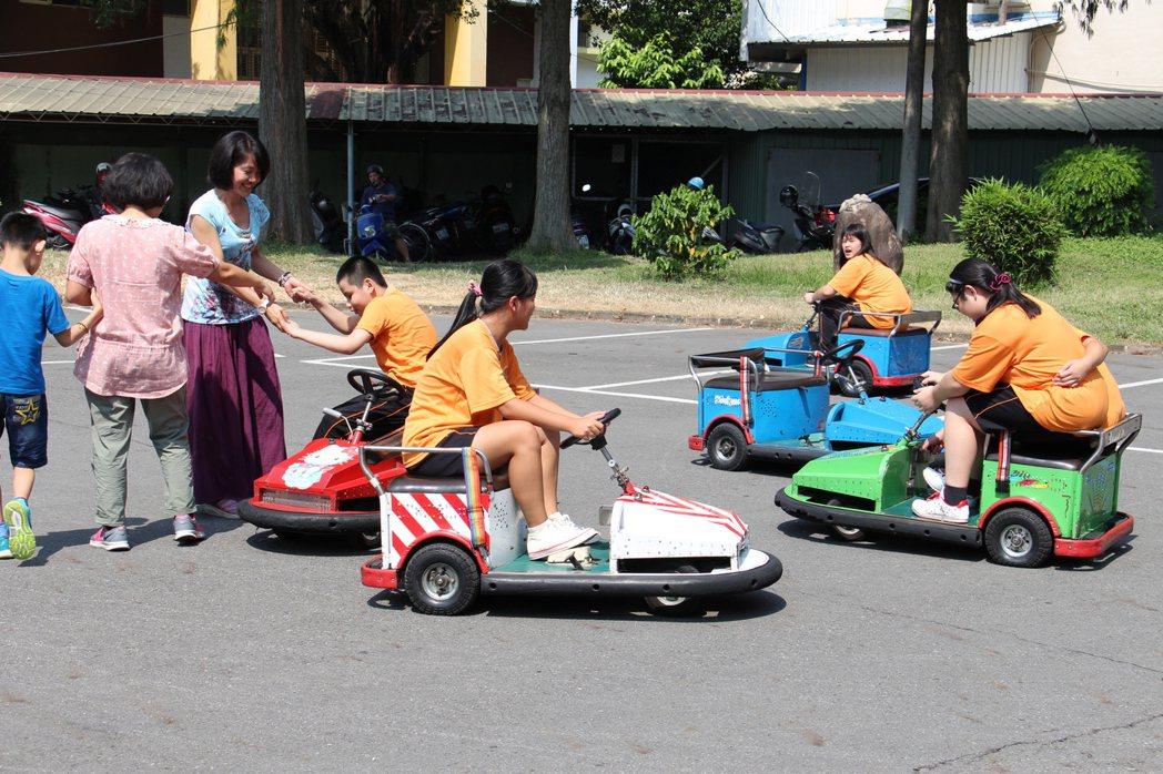 台中市助盲協會今日將夜市常見的遊樂器材搬到啟明學校,讓學生體驗碰碰車。記者洪上元...