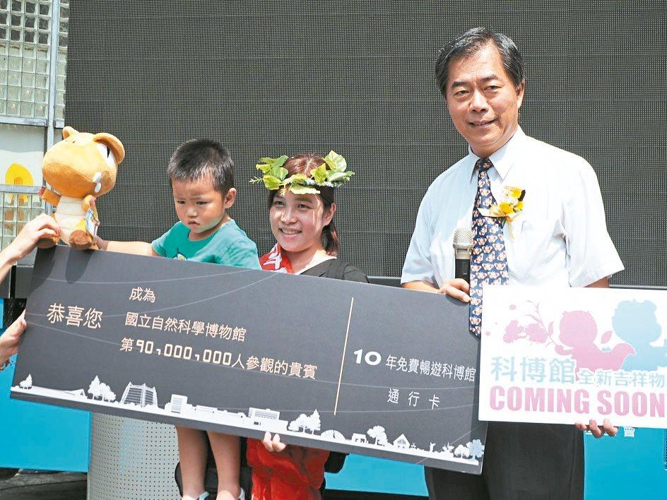 3歲的李庭佑(左)是科博館第9000萬名訪客,媽媽蕭佳美(中)受寵若驚,館長孫維...