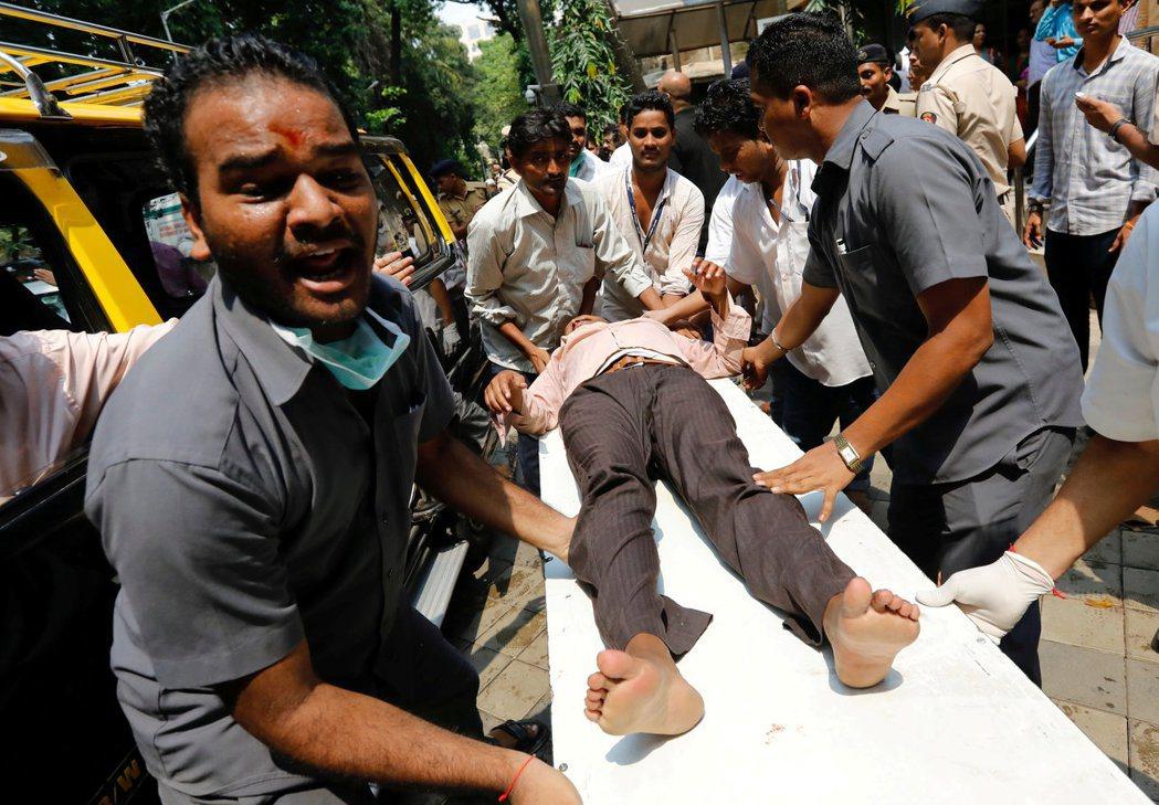 民眾幫忙將遭踩踏的傷者送醫。(路透)